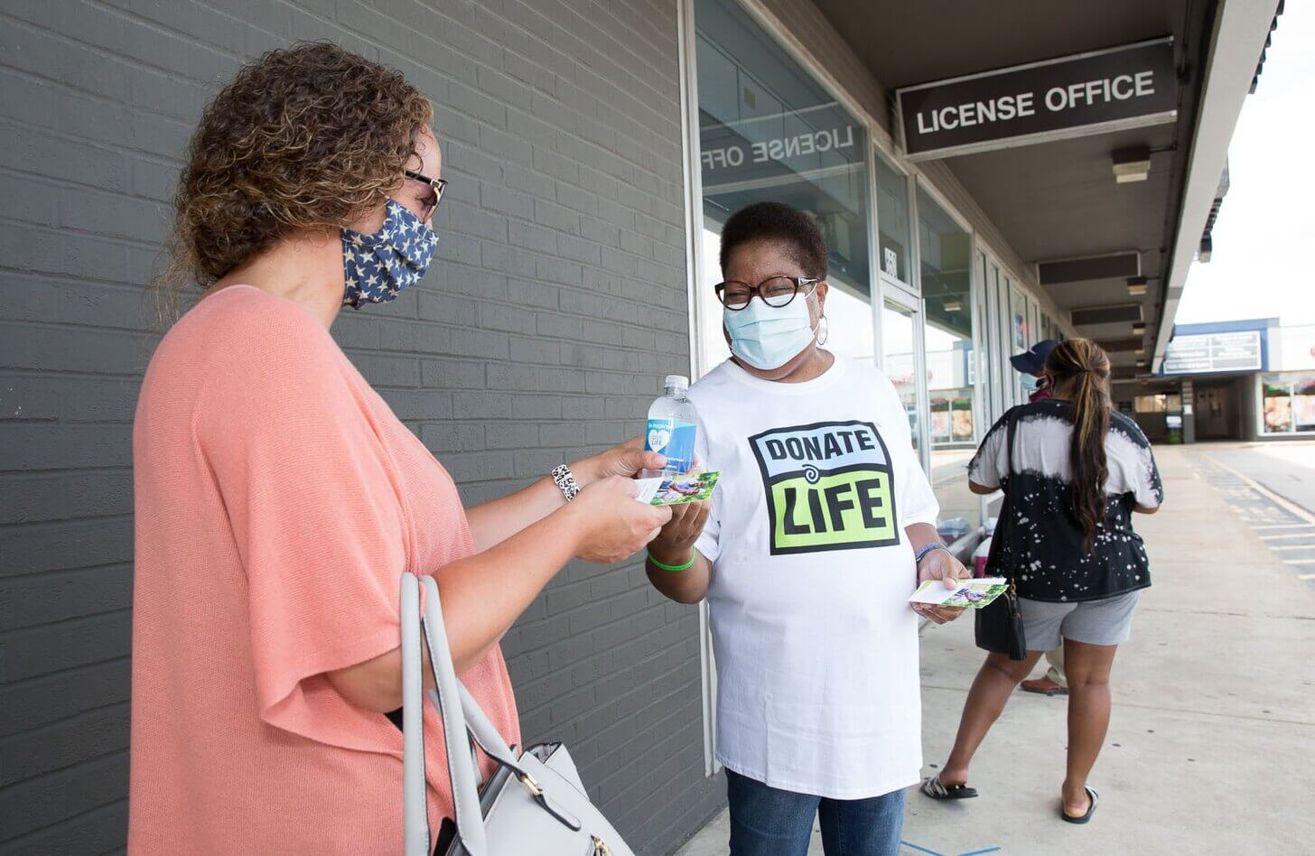 A Mid-America Transplant volunteer hands out water and information about organ and tissue donation at the Florissant DMV.